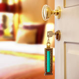 Hotel room. Or apartment doorway with key and keyring key fob in open door and bedroom in background