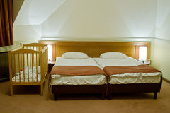 Hotel room with baby cot. Next to double bed Stock Photos