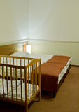 Hotel room with baby cot Stock Images