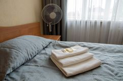 Hotel room. On the bed are three towels, soap, shampoo, shower gel royalty free stock images