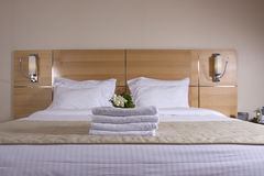 Hotel room bed and  white flowers Stock Photography