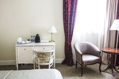 Hotel room in calm colours, desk and sitting area, armchairs Royalty Free Stock Image