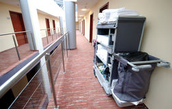 Hotel room cleaning trolley. Hotel room service trolley with all the towels, cleaning material standing at the side of the hallway (corridor Stock Images
