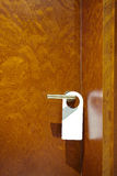 Hotel room closed door with white hanger, copy space. Stock Photography