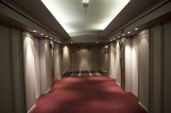 Hotel room corridor red carpet. Nice hotel corridor with red carpet and warm lighting Stock Photo