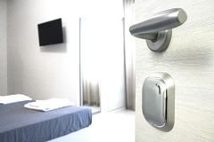 Hotel room door open. Clean and elegant accommodation service. Close up of handle. Bed, table and tv. Travel, lodging and motel concept stock photo