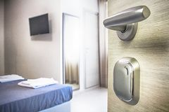 Hotel room door open. Clean and elegant accommodation service. Close up of handle. Bed, table and tv. Travel, lodging and motel concept stock photos