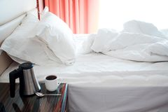 Hotel Room In Morning, Bed After Sleep, Kettle And Cup On The Bedside Table Royalty Free Stock Image