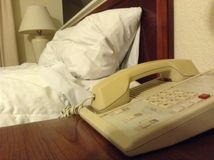 A Hotel Room. Including a phone, bed, and lamp royalty free stock image