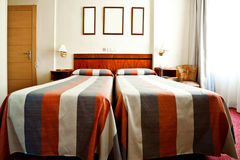 Hotel room interior with beds and frames Royalty Free Stock Photo