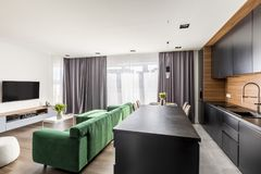 Hotel room interior with green lounge, TV set, windows with drapes and open space kitchen corner. Real photo of hotel room interior with green lounge, TV set stock photos