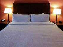 Hotel room interior with made bed and pillows with lamps on and a red wall royalty free stock photos