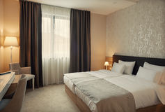 Hotel Room Interior. Modern interior of a hotel room for two, calm ambience with retro lamps and comfortable furniture Royalty Free Stock Images