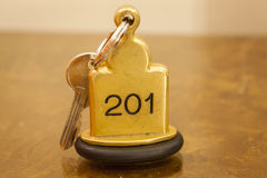 Hotel Room Key lying on Bed with keyring. Golden stock photo