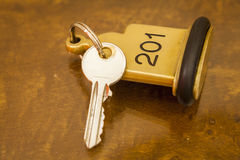 Hotel Room Key lying on Bed with keyring. Golden Stock Photography