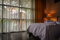 Hotel room with lamp and hanging wicker chairs outside the window royalty free stock photos