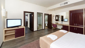 Hotel room with a large bed, a TV and some rooms Royalty Free Stock Photography