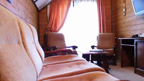 Hotel room luxury and superior. Suite room at the hotel. The room sofa, bed, table, chairs, TV, balcony. The house is made of wood stock footage