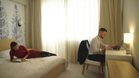 The hotel room,the man at the computer,girl reading magazine on bed stock video