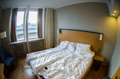 Hotel room with messed-up bed. Classic hotel room with messed-up bed and large window Stock Photos