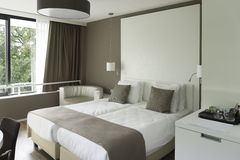Hotel room. New four star hotel room with a double bed. The room has large windows with view on trees. On the cabinet are cups for making thee or coffee. The Royalty Free Stock Images
