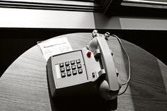 Hotel room phone. A corded phone on a table in a hotel room Royalty Free Stock Photo