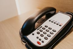 Hotel room phone on a wood desk royalty free stock photography