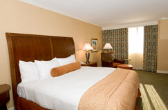 Hotel room with queen bed. Generic hotel/motel room with queen-size bed, patterned curtains and carpet Stock Photography
