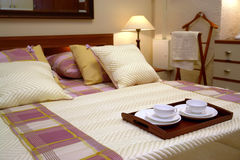Hotel room with room service. A view of a nicely color coordinated hotel room with a a room service meal on a tray resting at the foot of the bed Royalty Free Stock Photo