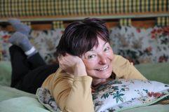 Hotel room senior woman on bed Royalty Free Stock Photo