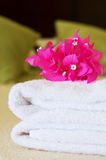 Hotel room service. White towels with flowers on a bed in a hotel room. Selective focus on flowers Stock Photos