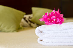 Hotel room service. White towels with flowers on a bed in a hotel room. Selective focus on flowers Stock Image