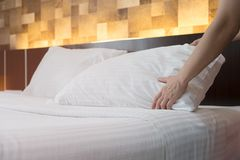 Hotel room service hands set up white pillow on the bed in the h stock image