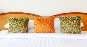 Hotel room setting with king sized bed, Thai silk orange and gre. En pillows in Thailand hotel Royalty Free Stock Image