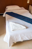 Hotel room setting with white bed Royalty Free Stock Photography
