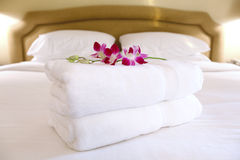 Hotel room settings. Towels neatly folded on the bed and decorated with orchids stock image