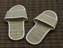 Hotel room slippers on rattan background. A worn out hotel  indoor slipper with a concept of relax and taking a break Stock Photography