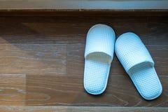 Hotel room slippers. Hotel room slippers on wooden floor Stock Photo