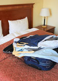 Hotel room with suitcase and clothes Stock Images