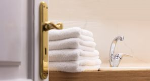 Hotel`s bathroom from open door. White towels folded next to the sink. Close up, blur backdrop. Hotel`s bathroom from open door. White towels folded on wooden royalty free stock photography