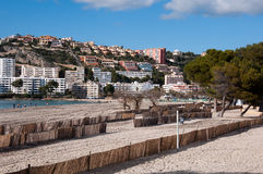 Hotel Scenery Of Santa Ponsa, Majorca, Spain. Image shows hotel scenery of Santa Ponsa, Majorca, Spain. In the front is a sandy beach with windbreakers. In the Royalty Free Stock Images