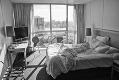 Hotel-Schlafzimmer mit ungemachter Bett-und Stadt-Ansicht Stockbild