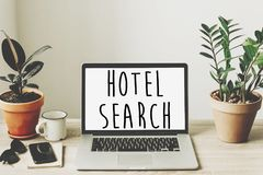 hotel search text on laptop screen on wooden desktop with phone, notebook, coffee and plant. booking hotel or apartment concept. royalty free stock photo