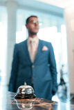 Hotel service bell at reception. Hotel welcomes you. Selective focus of modern luxury hotel reception desk with silver service bell and blurry silhouette of a Stock Photography