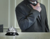 Hotel service bell and the receptionist. On the phone Royalty Free Stock Photo