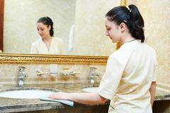 Hotel service. Female housekeeping worker cleaning table from dust in bathroom Stock Image