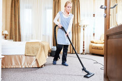 Hotel service. female housekeeping worker with vacuum cleaner Royalty Free Stock Photos