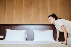 Hotel service. Made making bed in room. Royalty Free Stock Image