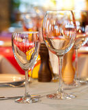 Hotel service: table in a restaurant with tablecloth, red napkins, wine glasses and cutlery. (soft focus - on the small glass) Stock Photography