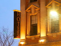 Hotel With Sign And Blowing Snow At Dusk Royalty Free Stock Photos